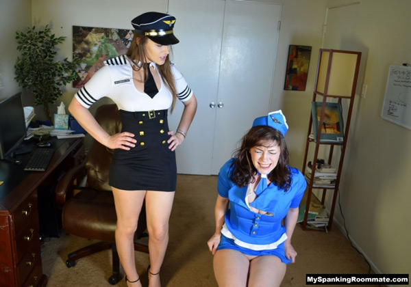 Air hostess, Kay Richards, sits down on her sore bottom while strict Dani Daniels watches in her pilot uniform