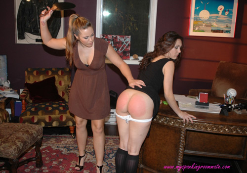 Sinn Sage bends over the desk and Madison spanks her with a leather paddle