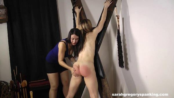 Sarah first gives her a hand spanking to warm her bare bottom up
