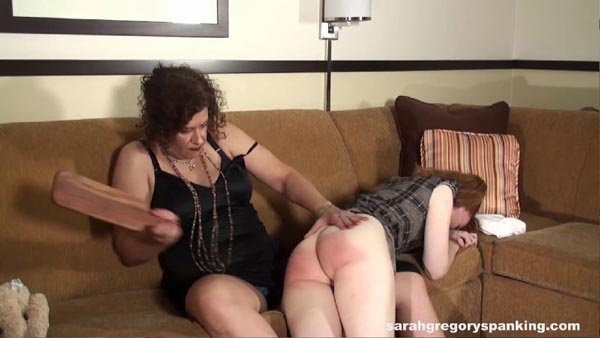 Miss Chris swings the leather paddle hard at Melody Nore's bare bottom