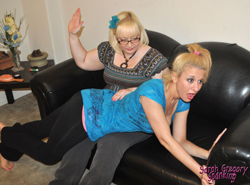 Sarah Gregory is spanked by big sister, Lily Starr, over her black pants
