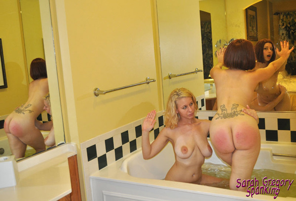 Busty Sarah Gregory kneels in the bath tub naked to spank Galas Loonar on the bare, wet bottom