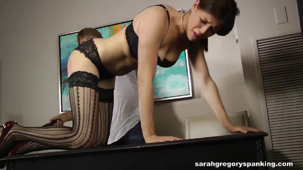 Zooey Zara is strapped while kneeling on all fours on the desk in her lingerie
