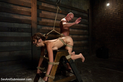Audrey Rose is tied naked over a spanking horse and her bare bottom is spanked