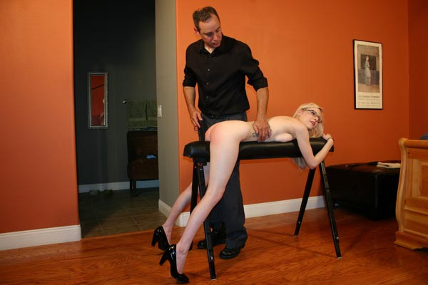 Arthur punishes slim blonde Violet October with a leather strap on the spanking bench