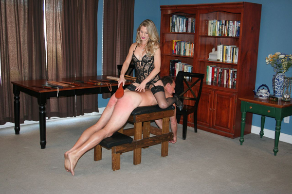 Mistress Aleana in sexy lingerie punishes a naked man over a spanking bench