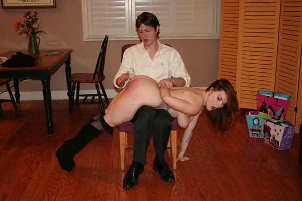 Summer Hart's wrist is held into the small of her back as she is spanked nude over the knee