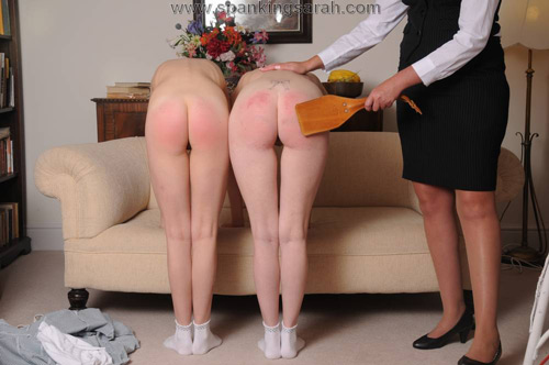Both schoolgirls bend over the sofa naked for the leather paddle