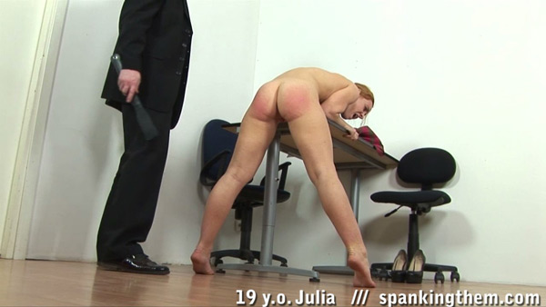 Julia bends over the desk naked for a nude strapping