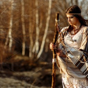 Shaman woman stands with magic stick in wilderness