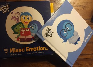 """Authentic AAC photo of Inside Out books with Sadness book leaning on the box of """"Mixed Emotions."""""""