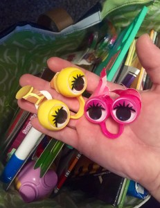 #AuthenticAAC picture of an adult hand holding google eye hand puppets over a bag of toys and books.