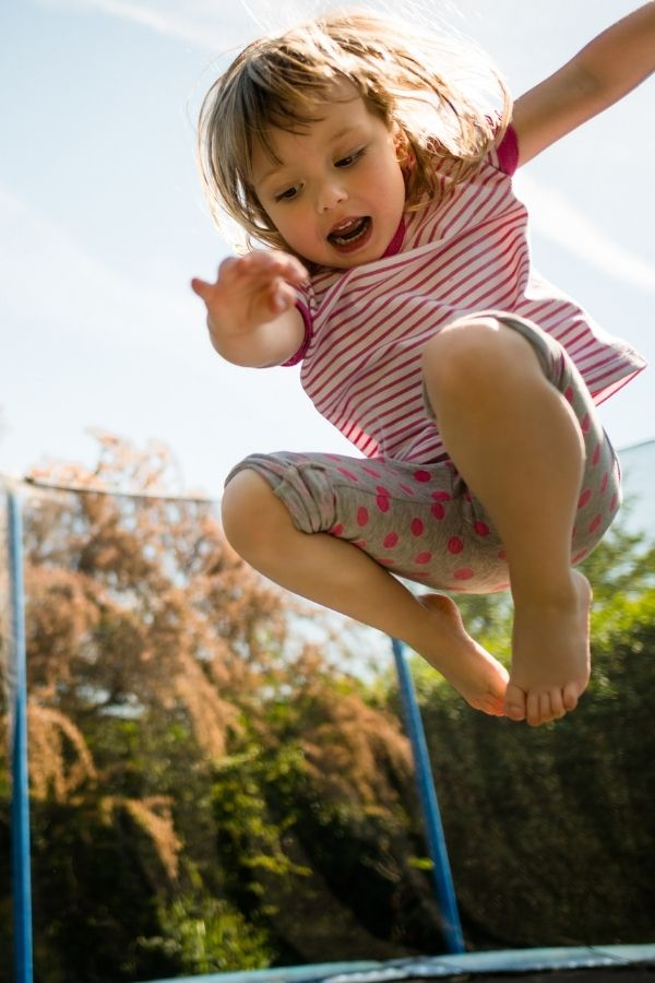 a young girl jumping on a trampoline