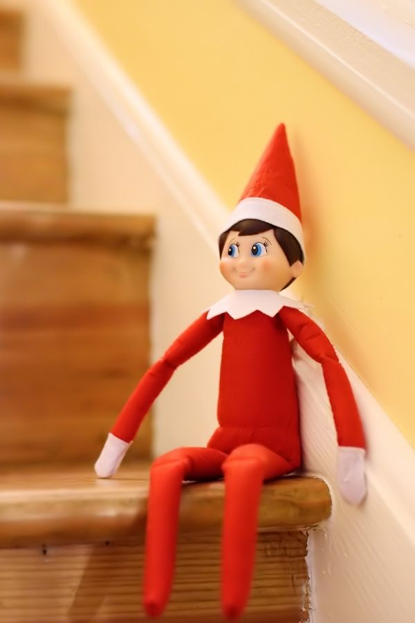 Elf on the Shelf sitting on the stairs