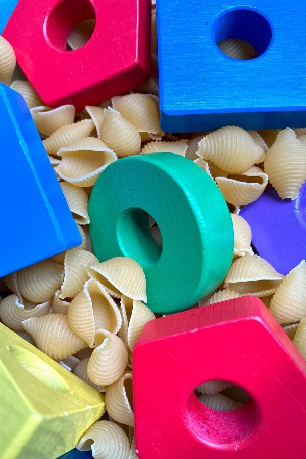 wooden shapes in dried pasta in a sensory box