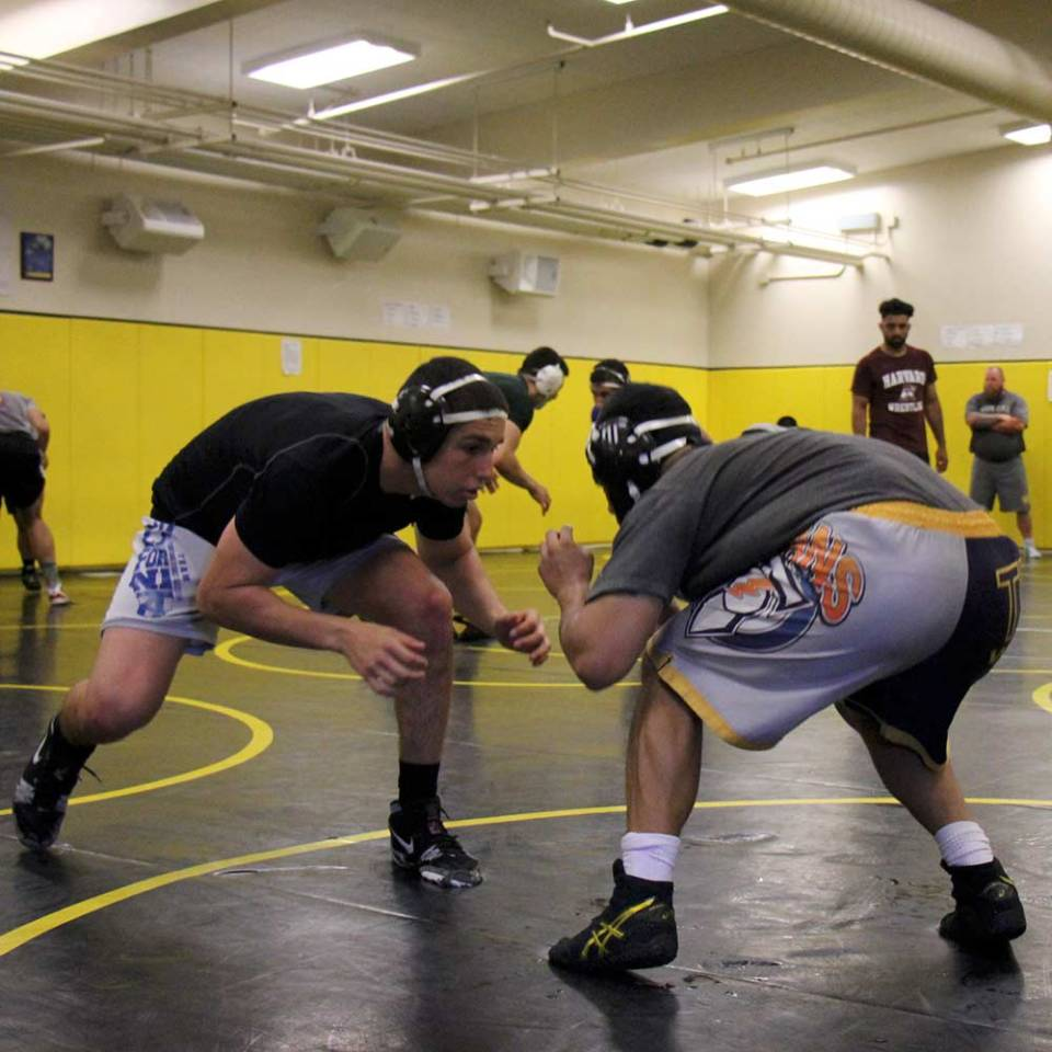 Chabot Gladiators Wrestling team practicing on mat with helmet gear, T-shirts, and shorts.