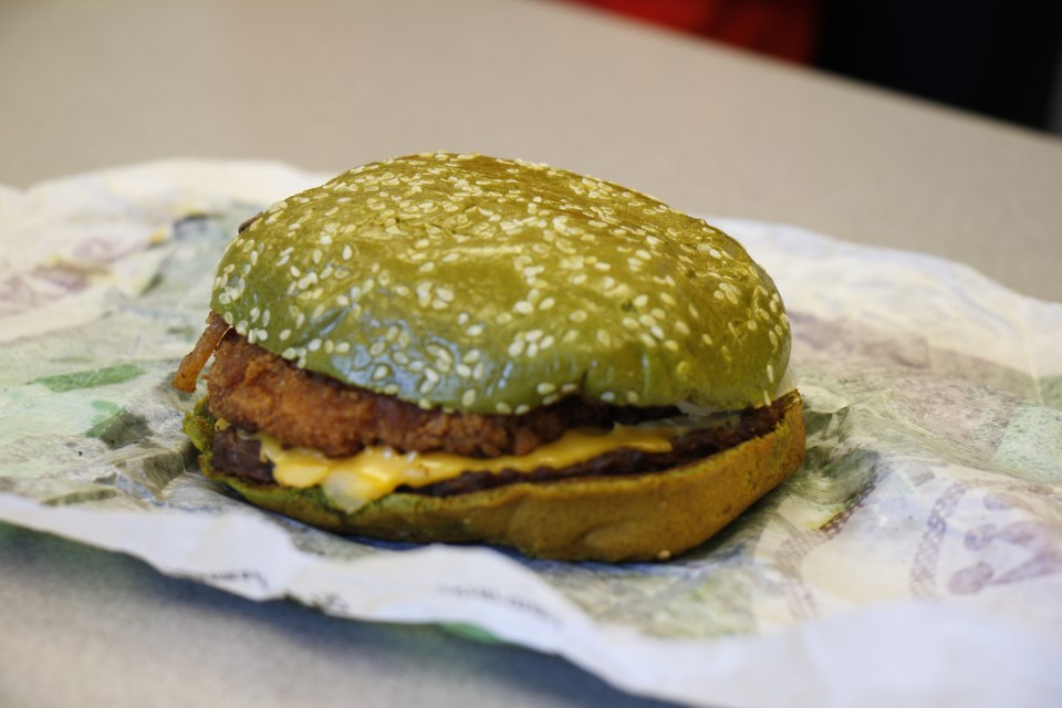 The Nightmare burger from Burger King, containing a beef patty, chicken patty, lettuce, tomato, onions, cheese, and bacon on a green-colored bun.