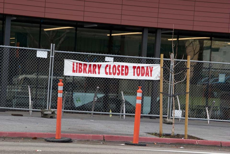 Banner with red text that Says Library closed on a fence with traffic cones in front