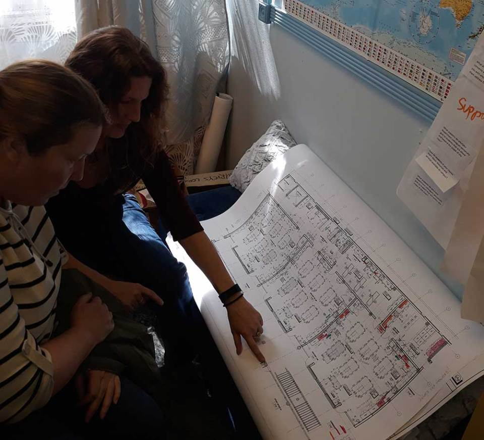 Science professors Jennifer Lange and Magen Jensen looking over the Chabot college Science building blueprints.