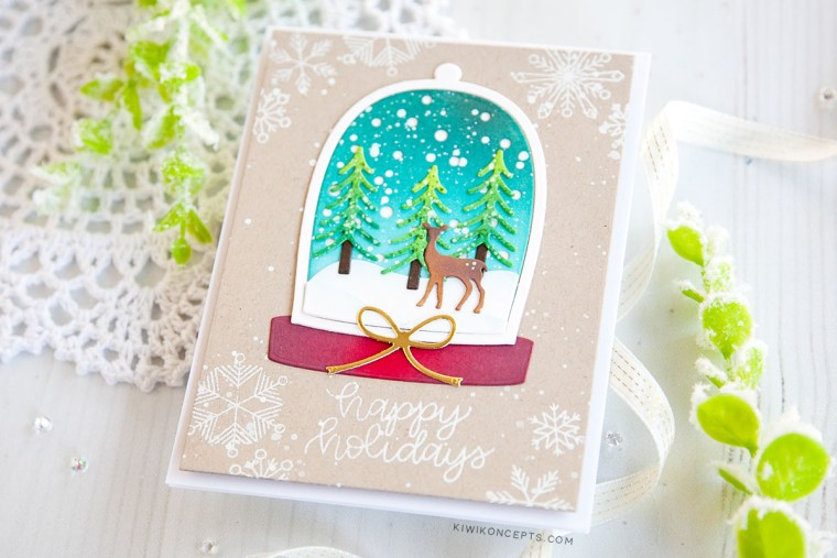 "Spellbinders Die D-Lites Holiday 2019 Inspiration | Clean & Simple Christmas Cards with Keeway Tsao. Keeway says: ""This card showcases the Shapeabilities Santa's Workshop dies. This die creates a beautiful little scene within a snow globe. I started by die cutting the snow globe frame and backing which was then ink blended with Peacock Feathers and Tumbled Glass distress oxide inks."""