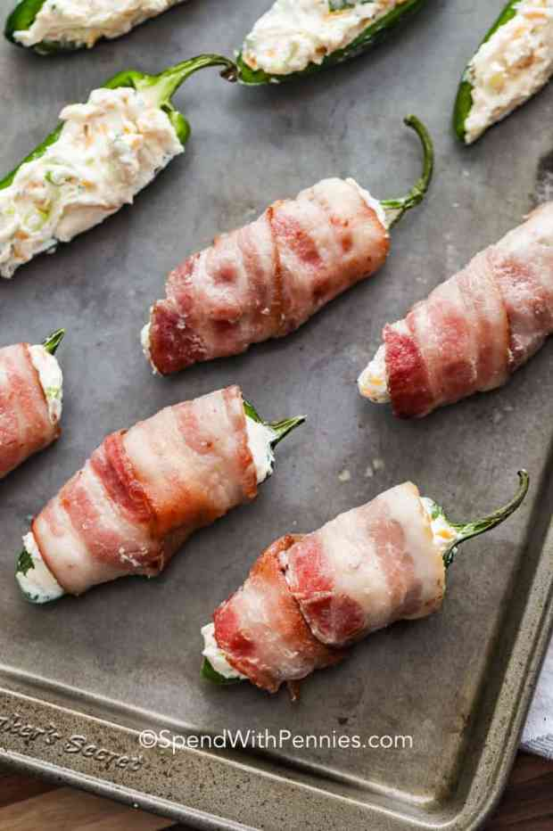A baking sheet with bacon wrapped jalapeno poppers ready to be grilled