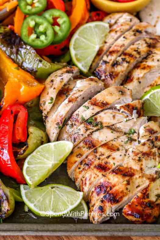 Sliced grilled chicken fajitas with limes and jalapenos