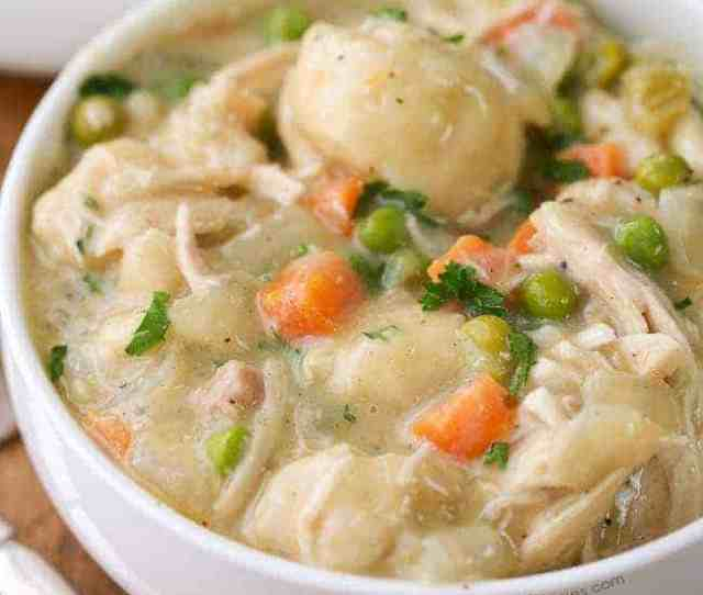Crockpot Chicken And Dumplings With Carrots Peas And Parsley Garnish In A White Bowl With