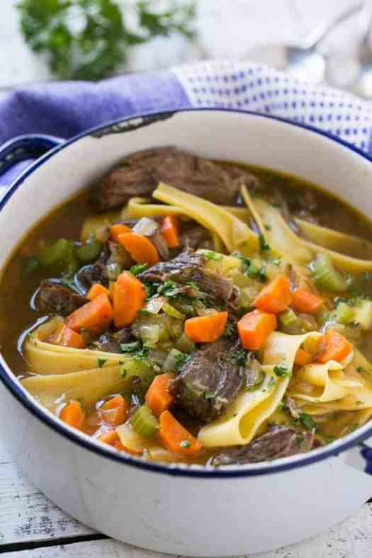 braised tender beef and Egg Noodle Soup with vegetables, and egg noodles in large pot