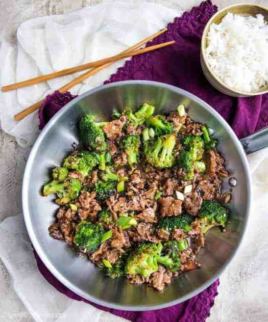 Beef and broccoli in a stainless steel skillet with bowl of rice with chopsticks in the background