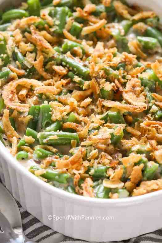A white casserole dish of colorful green bean casserole fresh from the oven, topped with crunchy crispy fried onions.