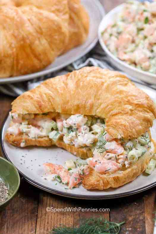 A creamy shrimp salad sandwich on a white plate with more shrimp salad and croissants in the background.
