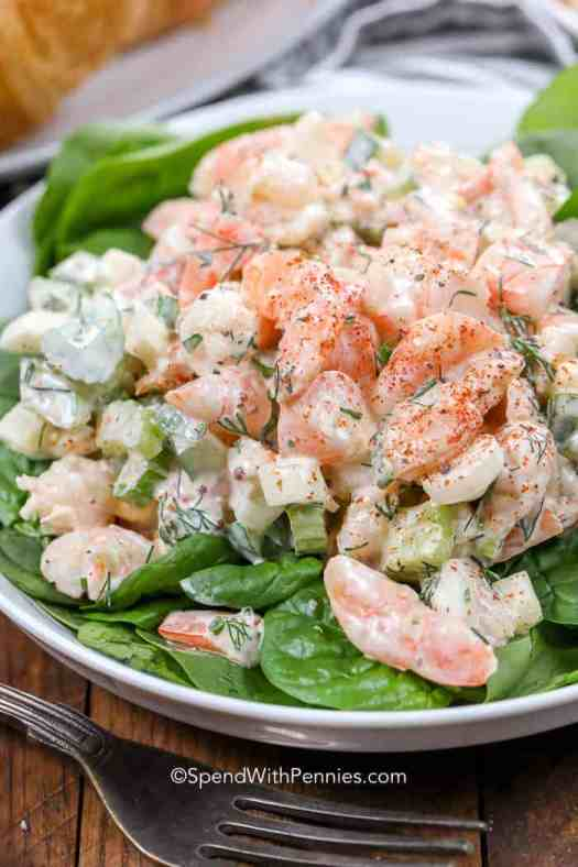 Fresh shrimp salad on a bed of lettuce on a white plate with a fork.