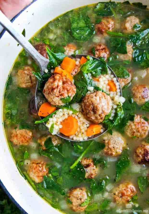 Ladle of Italian Wedding soup overtop of a white pot