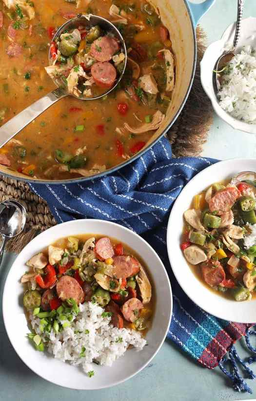 Overhead photo of chicken gumbo in two white bowls with chicken gumbo in a stock pot with a ladle.