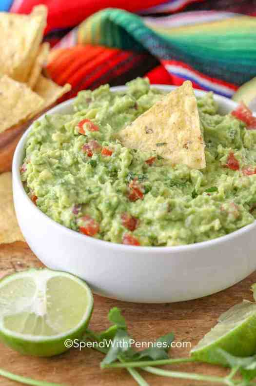 A bowl of the best homemade guacamole served with lime and chips.