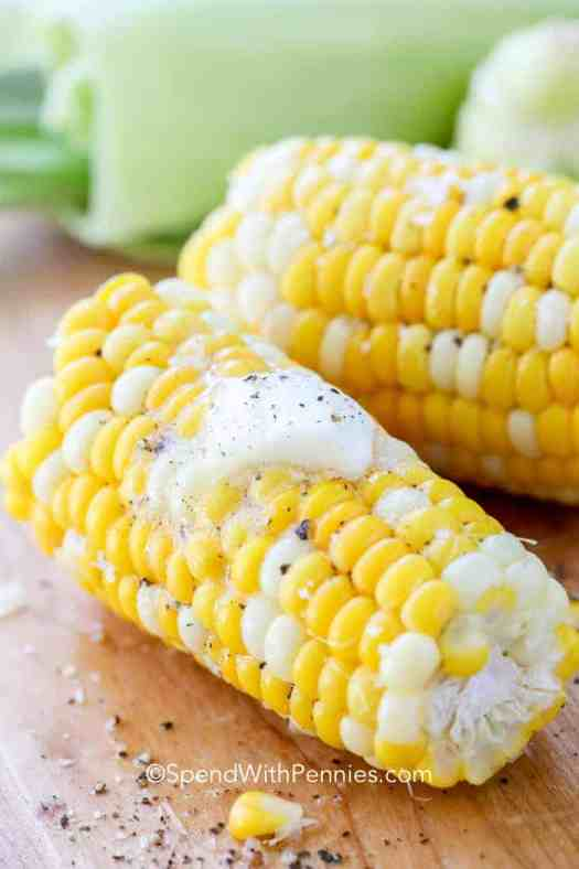 Microwaved cooked corn on the cob topped with butter, salt and pepper