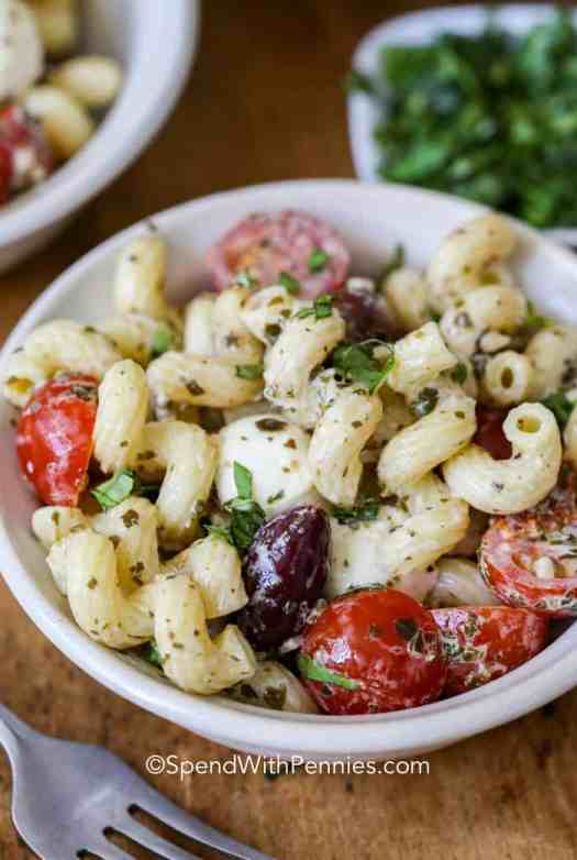 A serving of pesto pasta salad in a white bowl, garnished with basil.