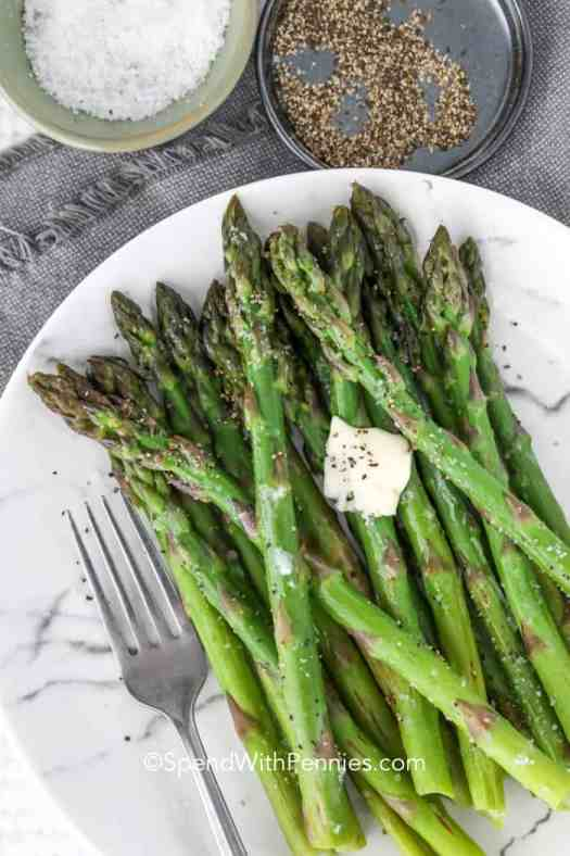 A plate of steamed asparagus with butter for serving