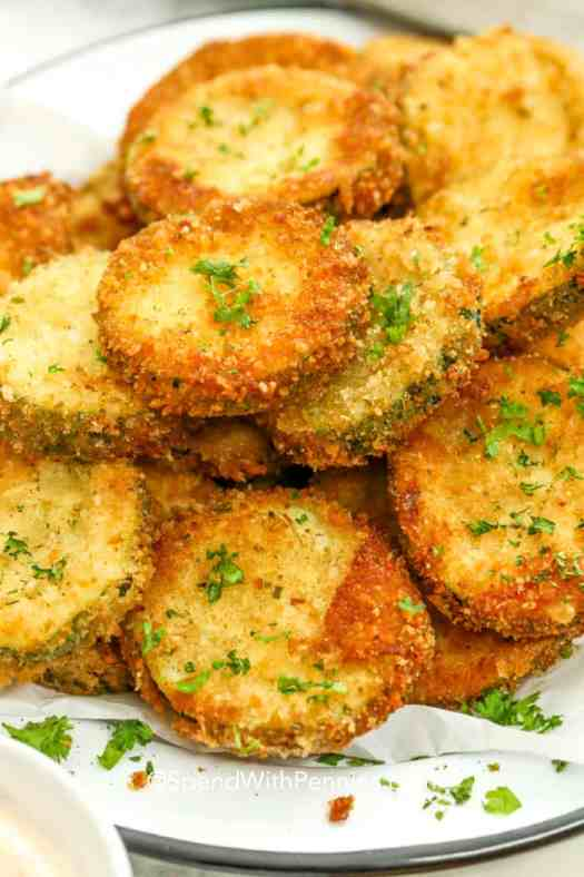 Fried zucchini chips stacked on a plate.