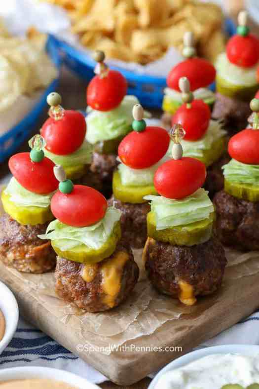 Close up of cheeseburger stuffed meatballs topped with pickles, lettuce, and tomatoes on a cutting board.
