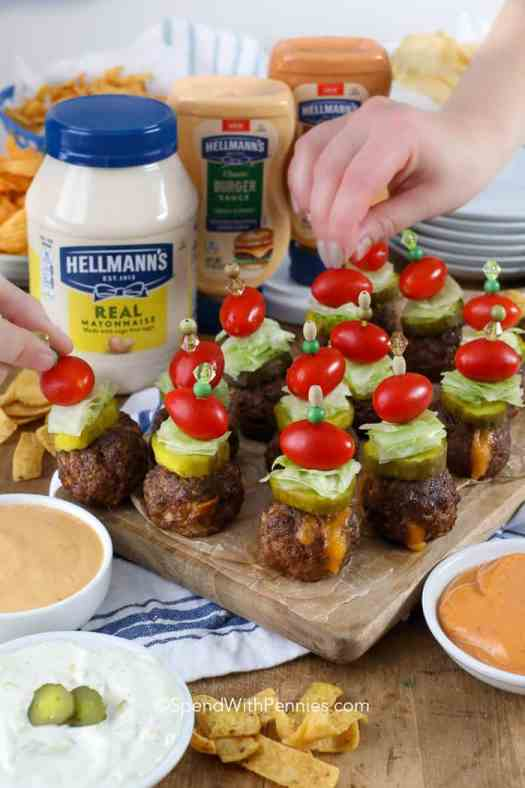 Cheeseburger stuffed meatballs on a skewer with pickles, lettuce and tomatoes.