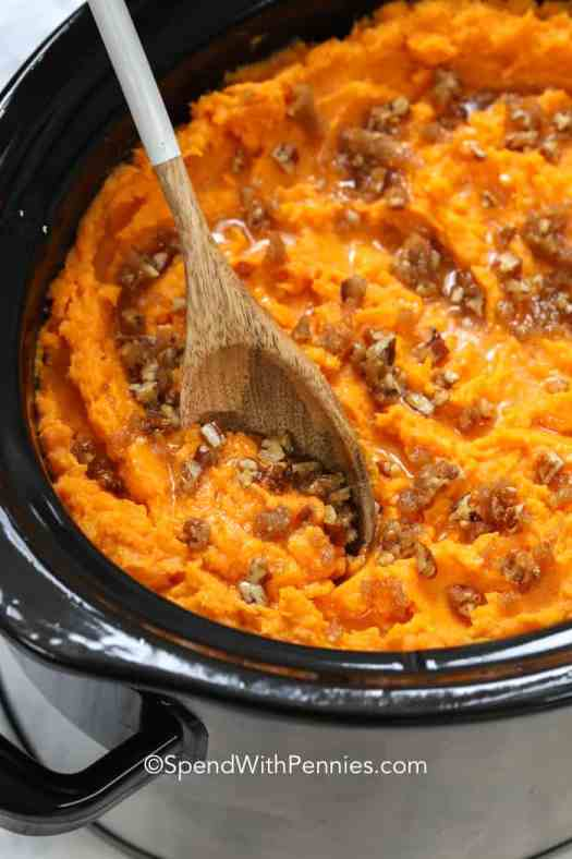 Slow cooker sweet potatoes potatoes and topped with brown sugar and pecans.