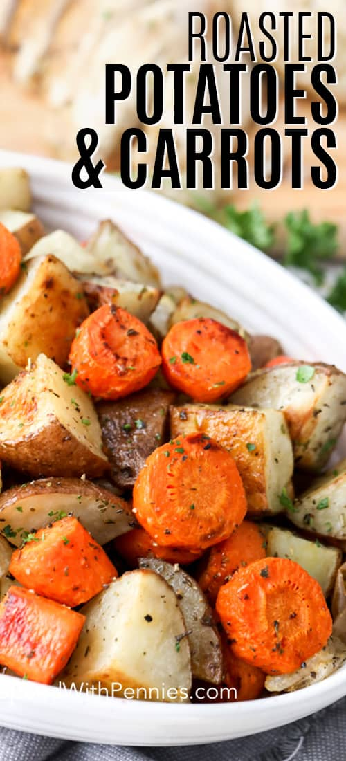 A serving dish with roasted potatoes and carrots, garnished with parsley.