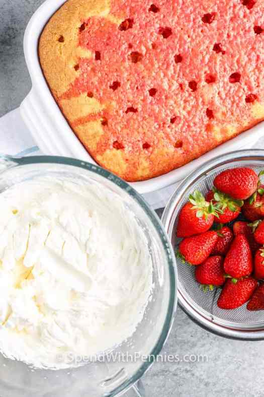 Strawberry Poke Cake with whipped topping and strawberries on the side