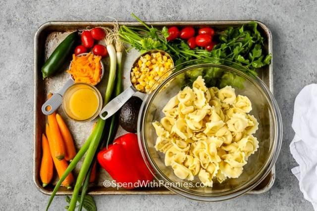 Tortellini Salad ingredients on a baking sheet