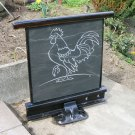 Cockerel carved in slate and mounted on a railway track frame