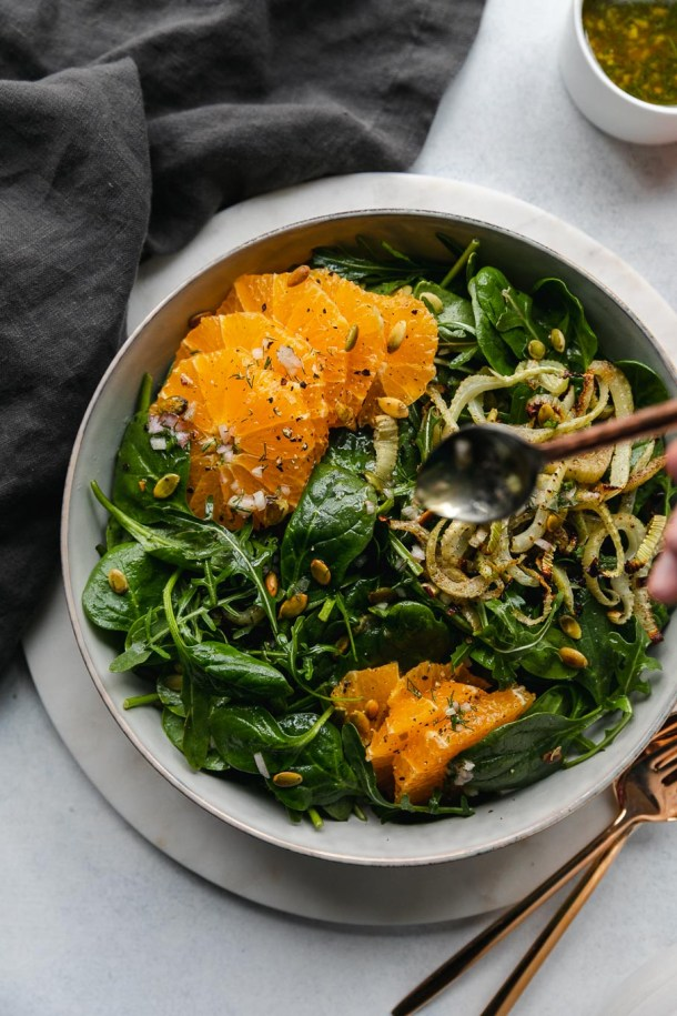 Overhead shot of a spinach arugula salad with roasted fennel, tangelos, and toasted pumpkin seeds with a spoon drizzling dressing on it