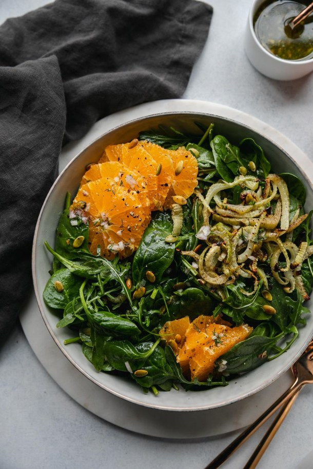 Overhead shot of a spinach arugula salad with roasted fennel, tangelos, and toasted pumpkin seeds