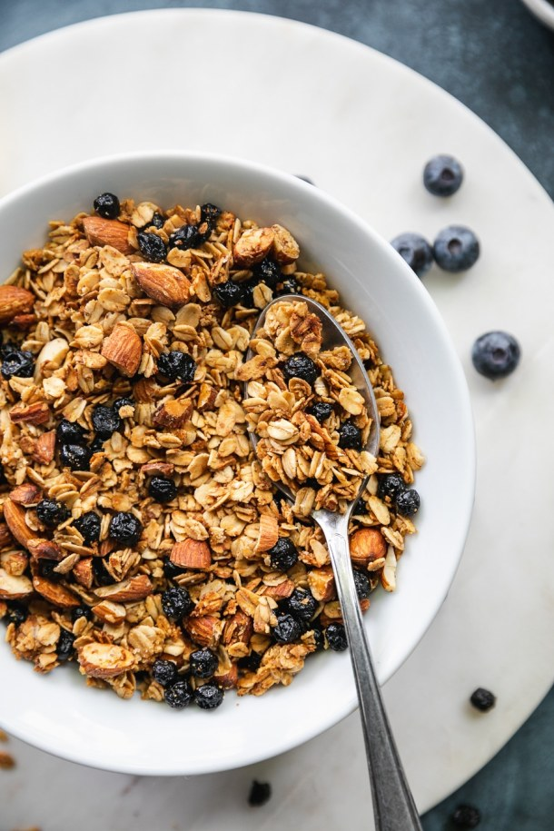 Overhead close up shot of a bowl of lemon blueberry granola with a spoon in the bowl