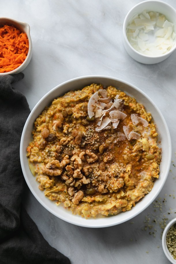 Overhead shot of a bowl of carrot cake oatmeal garnished with coconut flakes, maple syrup, golden raisins, walnuts, and hemp seeds